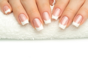 Beautiful fingers with french manicure on the towel.