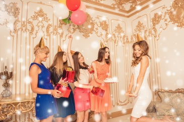 Group of girls with cake and presents congratulating their friend