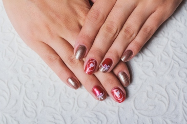 Festive nail art in pink and gold colors on light background