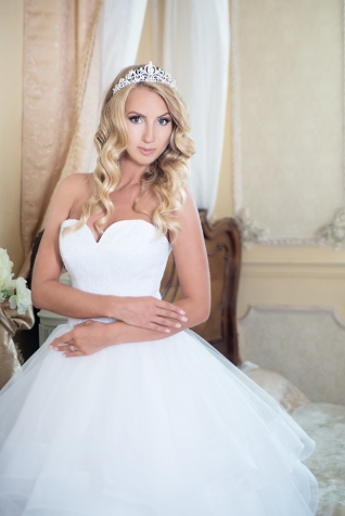 Bride in wedding dress with crown in interior. Blonde